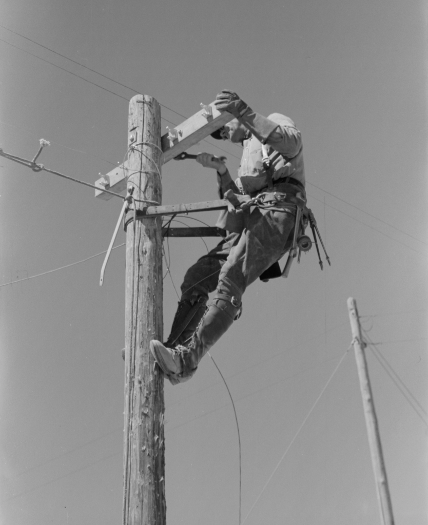Lineman on telephone pole at the Casa Grande Valley Farms, Pinal County, Arizona (Libary of Congress, LC-USF33-012683-M5)